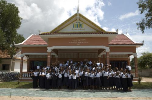 建設された学校の前で喜ぶ現地の子どもたち