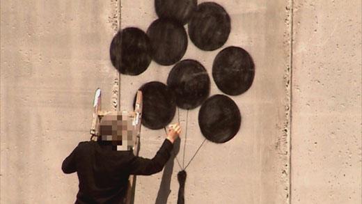 イスラエルとパレスチナを分離する壁に作品を描くバンクシー © 2010 Paranoid Pictures Film Company All Rights Reserved.